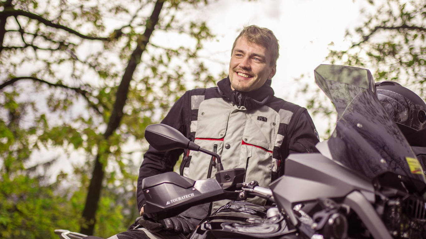 The dguard brand ambassador on a Honda Africa Twin stands in the woods and smiles. (Photo: digades GmbH))
